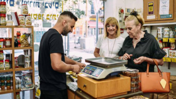 Local shopkeepers in Jaffa celebrating digital coin campaign success